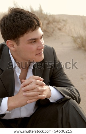 young guy sitting on the sand and smiles - stock photo