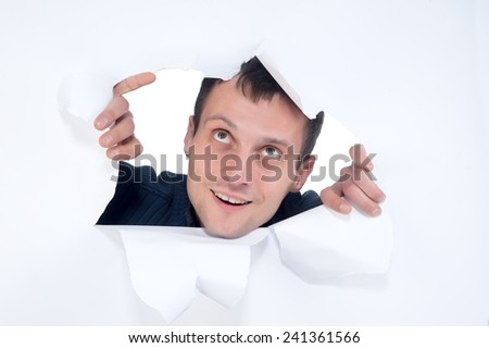 Young guy sticks his head through a hole in a sheet of paper - stock photo