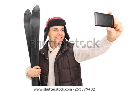 Young guy taking a selfie with his skis isolated on white background - stock photo