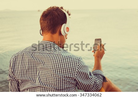 young guy with a beard in a shirt and headphones listens music sitting on the pier in his hand a smartphone with player,Young man wearing white blank t-shirt and blue jeans, vintage style, - stock photo