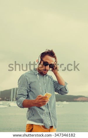 young guy with a beard in sunglasses shirt and shorts listening to music in headphones on a smartphone on the pier near, listen  music.headphones,shirt,style,casual,mans style - stock photo