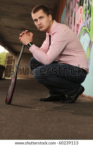 young guy with baseball bat sitting under bridge - stock photo