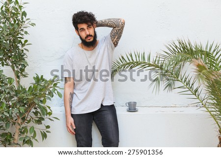 young guy with beard and tattooed arm posing - stock photo