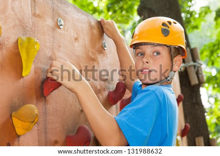 Young guy with  climbed equipment on the top of climbing wall. - stock photo
