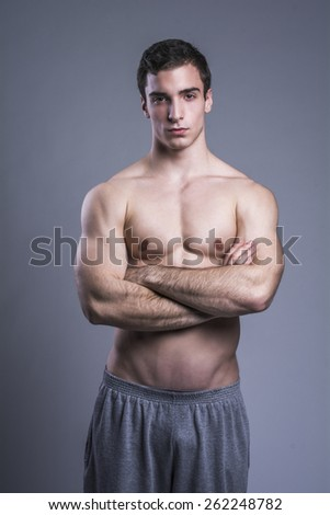 Young guy with crossed arms looking at the camera in the studio - stock photo