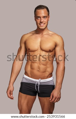 Young guy with great body anatomy in black swim shorts possing in studio. Light grey background.