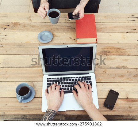 young guy with tattooed arm using a laptop while his friend using a smartphone - stock photo