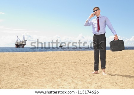 young guy with the phone on the background of oil rigs
