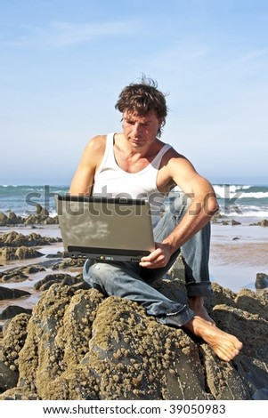 Young guy working on his laptop on a rock at the beach - stock photo