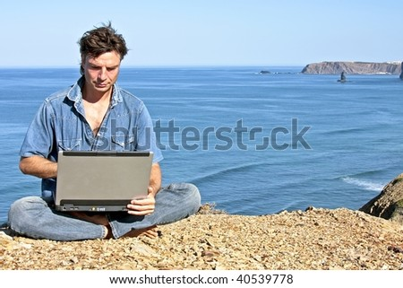 Young guy working on his laptop on a rock at the ocean - stock photo