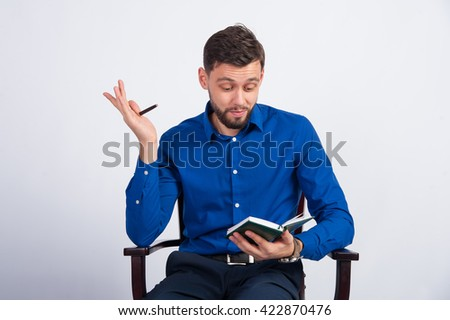 young guy writes ideas in a notebook - stock photo