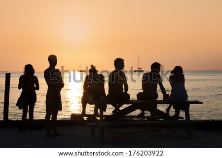 Young guys enjoying the sunset on the beach - stock photo