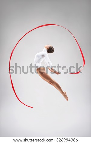 Young gymnast jumping in the studio - stock photo