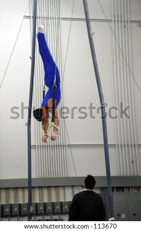 Young gymnast practicing on rings - stock photo