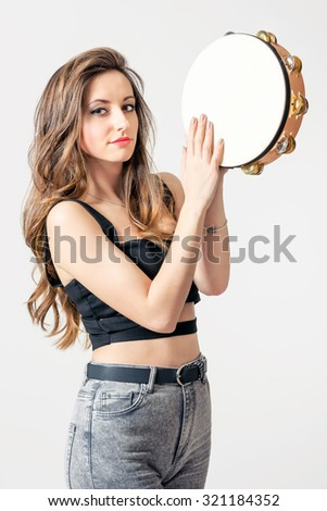 Young gypsy with tambourine in her hands, close-up - stock photo