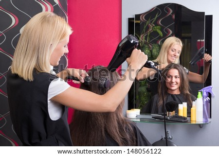 young hairdresser with hairdryer and hairbrush drying female hair in salon - stock photo