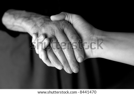 Young hand give help to old hand - stock photo