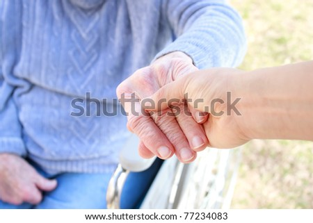 Young hand giving a dandelion to senior's hand - stock photo