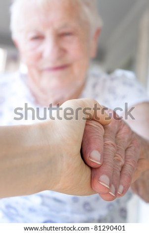 Young hand holding senior lady's hand - stock photo