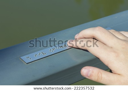 Young hand reading braille writing - stock photo