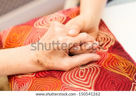 Young hands caring for old hands on a red cushion - stock photo