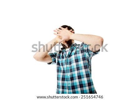 Young handsome afraid man covering his face. - stock photo