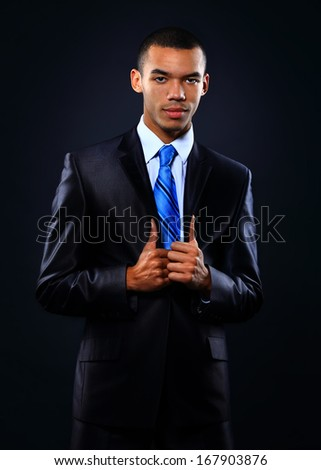 Young handsome African-American businessman in black suit. - stock photo