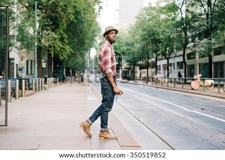 young handsome afro black man standing on the edge of the sidewalk, he is going to cross the street, looking right, smartphone handheld