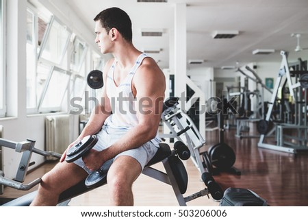 Young handsome and attractive adult man exercising and doing weight lifting at fitness gym. Sport training indoors.