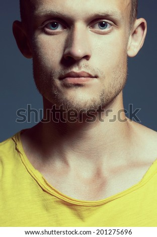 Young handsome and blue-eyed man with pensive look in bright yellow T-shirt posing over grey background. Close up. Studio shot - stock photo