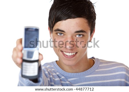 Young handsome and smiling male teenager shows mobile phone into camera. Isolated on white. - stock photo