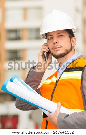 young handsome architect supervising a construction talking on cell phone outdoors - stock photo
