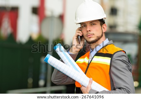 young handsome architect supervising a construction using cell phone with buildings in the background - stock photo