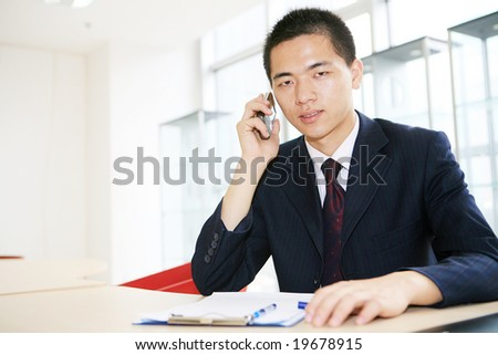 young handsome asian business man calling  in office