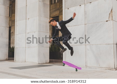 Young handsome Asian model dressed in dark suit and tie jumping with his skateboard - stock photo