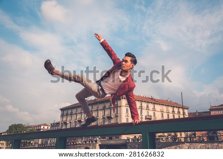 Young handsome Asian model dressed in red blazer jumping a balustrade - stock photo