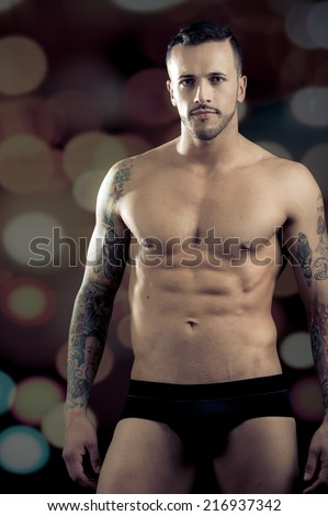 Young handsome athletic male model wearing underwear over dark background - stock photo