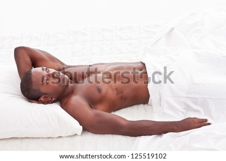 Young handsome Athletic muscular ethnic black Afro-American man resting in bed - stock photo