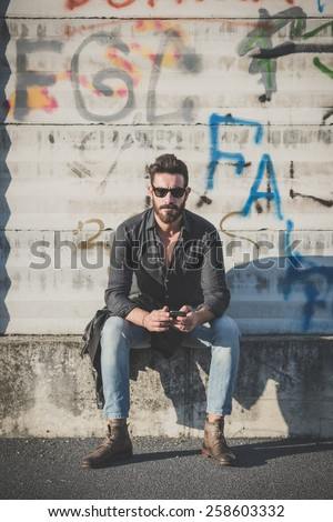 young handsome attractive bearded model man using smartphone in urban context - stock photo