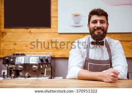 Young handsome barista with beard in shirt and bow tie smiling while standing at the bar counter - stock photo
