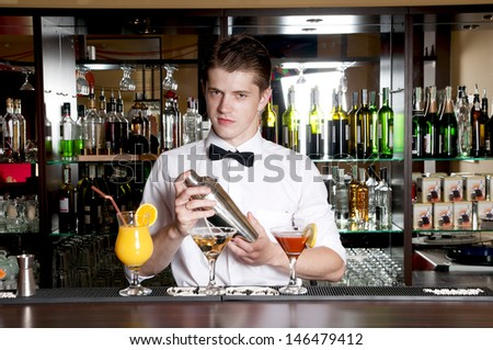 Young handsome barman standing in front of the bar and making cocktail drinks. - stock photo