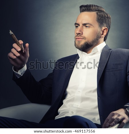 Young handsome bearded caucasian man sitting on chair with a cigar. Perfect skin and hairstyle. Wearing grey suit and watch. Studio portrait on gradient black to grey background. Toned