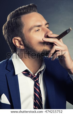 Young handsome bearded caucasian man sitting on chair with a cigar. Perfect skin and hairstyle. Wearing blue suit and tie. Studio portrait on gradient black to grey background. Toned