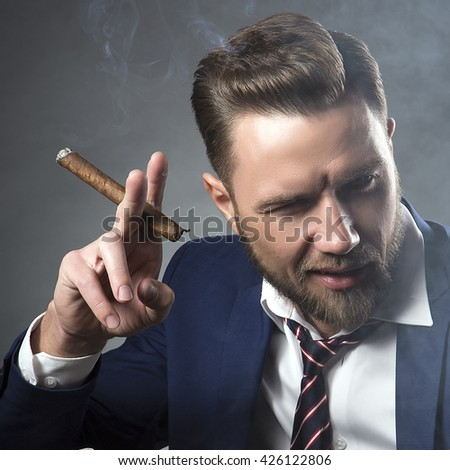 Young handsome bearded caucasian man sitting on chair with cognac and a cigar. Perfect skin and hairstyle. Wearing blue suit and watch. Studio portrait on gradient black to grey background. Toned