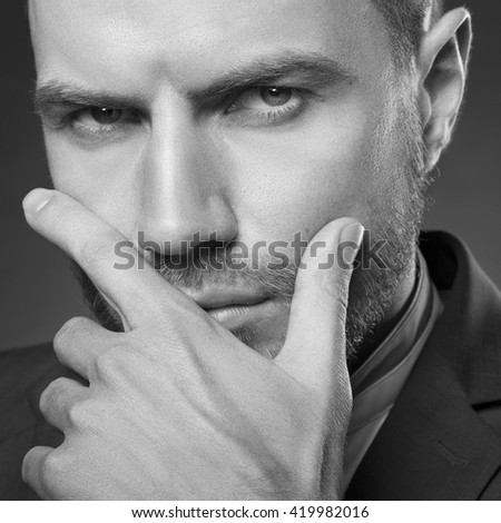 Young handsome bearded caucasian man with blue eyes and a hand near chin. Perfect skin and hairstyle. Wearing blue suit and watch. Studio portrait on gradient black to grey background. Black and white