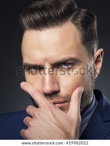 Young handsome bearded caucasian man with blue eyes and a hand near chin. Perfect skin and hairstyle. Wearing blue suit and watch.  Studio portrait on gradient black to grey background. Toned