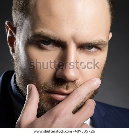 Young handsome bearded caucasian man with blue eyes and a hand near chin. Perfect skin and hairstyle. Wearing blue suit. Studio portrait on gradient black to grey background.