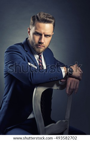 Young handsome bearded caucasian man with blue eyes sitting on chair. Perfect skin and hairstyle. Wearing blue suit and watch. Studio portrait on gradient black to grey background. Toned
