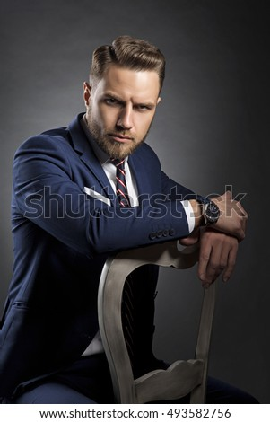 Young handsome bearded caucasian man with blue eyes sitting on chair. Perfect skin and hairstyle. Wearing blue suit and watch. Studio portrait on gradient black to grey background.