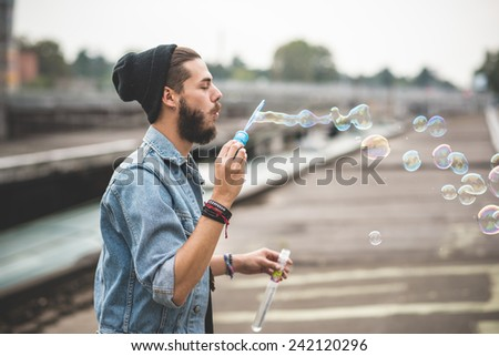 young handsome bearded hipster man blowing bubbles soap in the city - stock photo